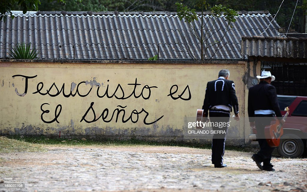 Two musicians walk by a house with a graffiti reading 'Jesuschrist is the Lord' in Valle de Angeles, a tourist municipality 22 km northwest of Tegucigalpa, on March 3, 2013. AFP PHOTO/Orlando SIERRA