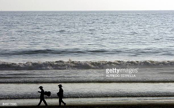 Two musicians walk on the beach before an ATP Open tennis match in Acapulco Mexico on February 22 2009 AFP PHOTO/Alfredo ESTRELLA