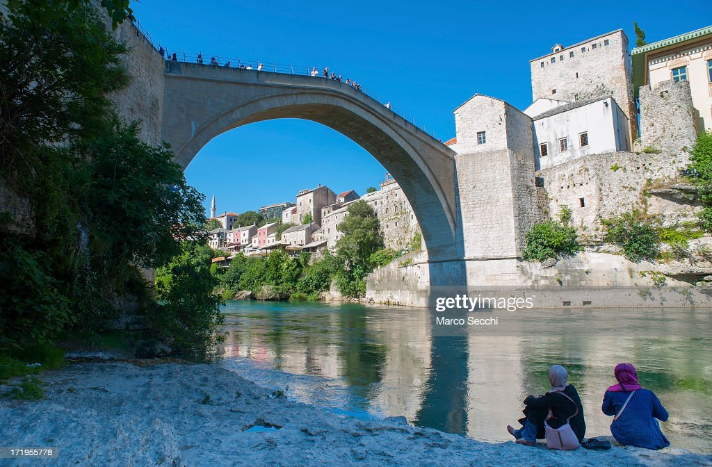 Two Muslim girls sit on the bank of the Neretva river under the Old Bridge as the city of Mostar remembers the 1993 conflict on June 28, 2013 in Mostar, Bosnia and Herzegovina. The Siege of Mostar peaked in 1993 during the Croat-Bosniak conflict lasting eighteen months as fighting took place as Bosnia and Herzegovina declared independence from Yugoslavia. The city was divided in half between the two battling armies. Mostar, dating back over four hundred years, was mostly destroyed through the fighting. Although reconstruction has slowly commenced in the last decades, evidence of the war remains in bullet ravaged buildings still standing throughout the city.