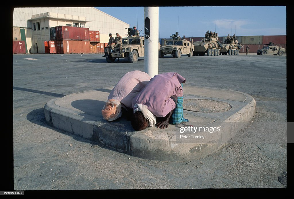 Two Muslim men kneel and pray at a Mogadishu airport as American troops arrive to deal with civil war and famine In the 1980s warlord factions joined...