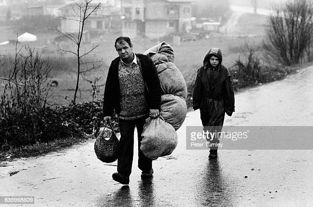 Two Muslim refugees with heavy bundles walk along a wet road After the fall of Communism in 198990 Yugoslavia broke into Croatia Bosnia and Serbia...