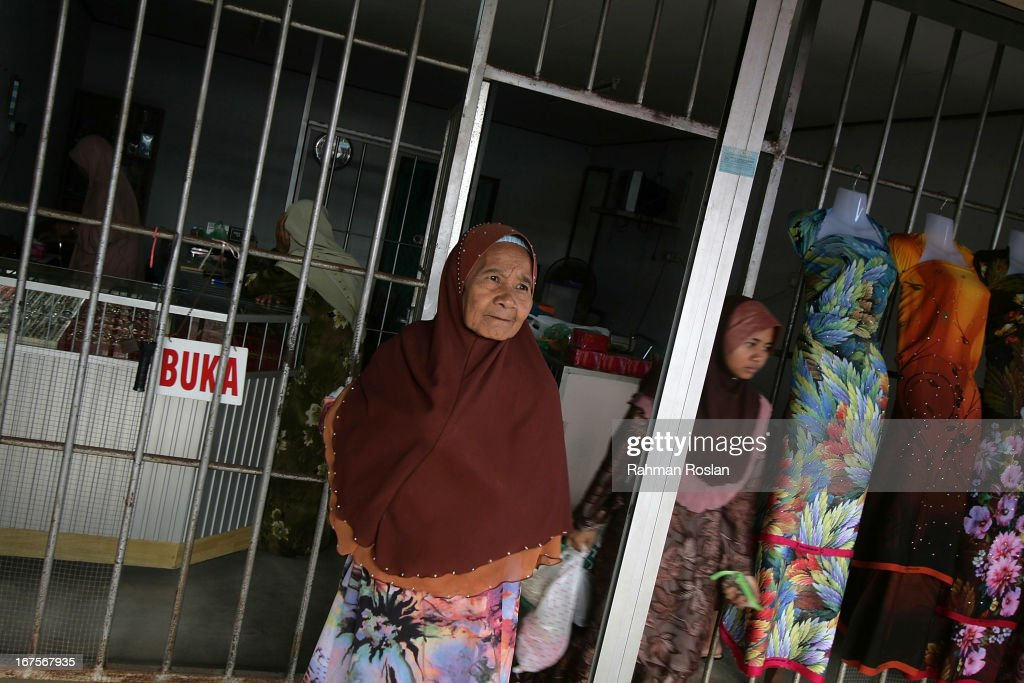 Two muslim women dash out from a goldsmith to attend Hadi Awang's weekly friday sermon on April 26, 2013 in Rusila, Malaysia. Malaysia's 13th general election will be held on May 5.