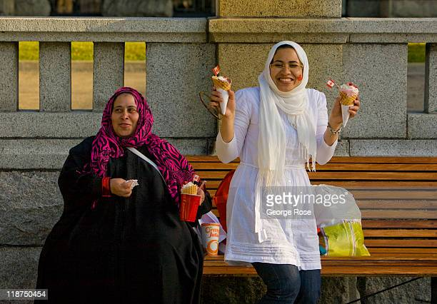 Two Muslim women eat ice cream while awaiting the Canada Day inner harbour fireworks show on July 1 2011 in Victoria British Columbia Canada The...