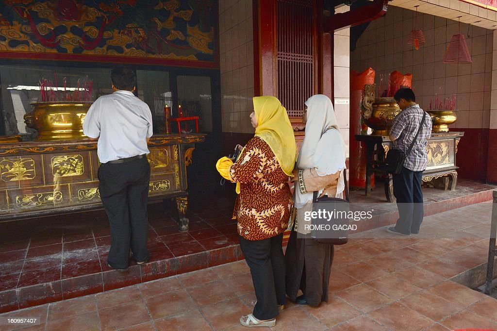Two Muslim women Lusi Kusuma (L) and Widi Astuti (R) visit a Buddhist temple in the Indonesian capital city of Jakarta on February 8, 2013 as the Muslim majority country's minority Chinese-Indonesians prepare to celebrate the Chinese Lunar New Year. The 'Year of the Snake' falls across the region on February 10, 2013.