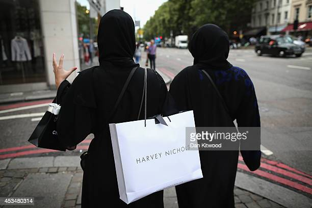 Two muslim women wearing black Abayas and head scarfs walk through Knightsbridge holding fashionable shopping bags on August 6 2014 in London England...