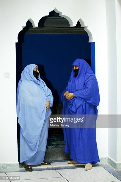 Two Muslim women wearing the traditional chador or nikab (full body cloak) standing under curved archway entrance of house, Morocco. (MR)
