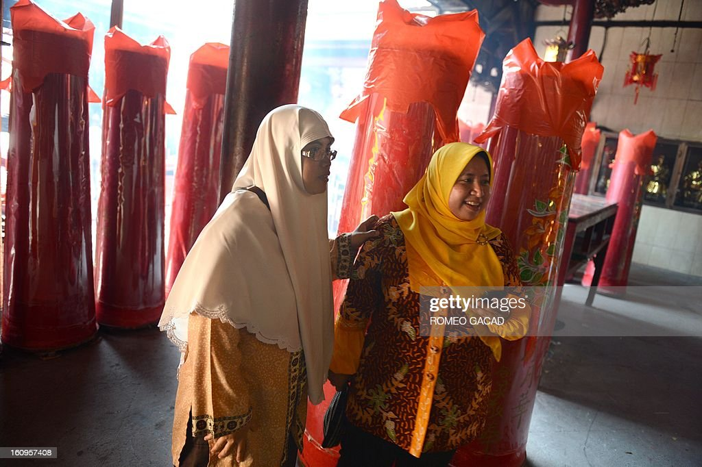 Two Muslim women Widi Astuti (L) and Lusi Kusuma (R) visit a Buddhist temple in the Indonesian capital city of Jakarta on February 8, 2013 as the Muslim majority country's minority Chinese-Indonesians prepare to celebrate the Chinese Lunar New Year. The 'Year of the Snake' falls across the region on February 10, 2013.