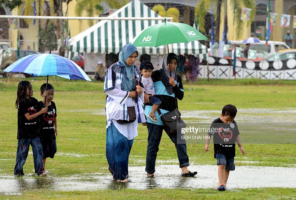 Two Muslim women with their children make their way across a flooded field to listen to opposition leader Anwar Ibrahim speak after Friday prayers at a election rally in Ulu Melaka, on the northern Malaysian island of Langkawi on May 3, 2013. Cast into the political wilderness 15 years ago by Malaysia's regime, Anwar Ibrahim faces his best and possibly last shot at vengeance in climactic elections on May 5. AFP PHOTO / GOH CHAI HIN