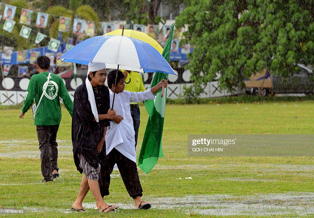 Two Muslim youths make their way across a flooded field to listen to opposition leader Anwar Ibrahim speak after Friday prayers at a election rally in Ulu Melaka, on the northern Malaysian island of Langkawi on May 3, 2013. Cast into the political wilderness 15 years ago by Malaysia's regime, Anwar Ibrahim faces his best and possibly last shot at vengeance in climactic elections on May 5.