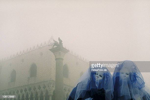 Two mysterious carnival masks with blue veil in foggy Venice