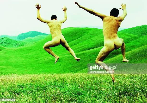 Two Naked Men Jumping in a Field