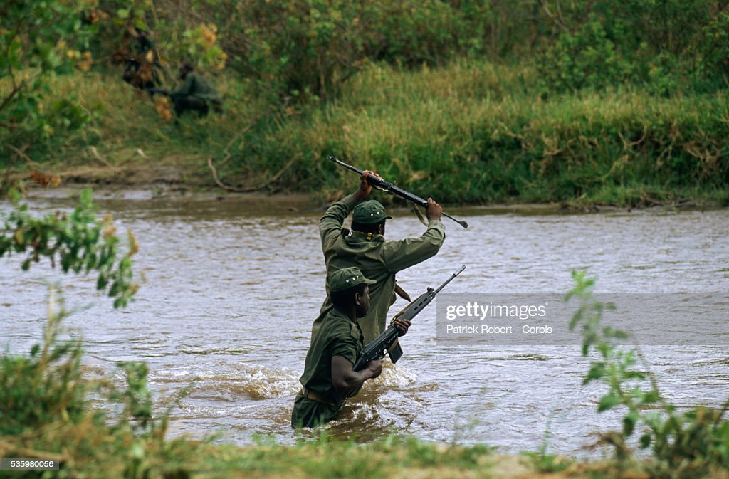 Two National Parks Guards in search of poachers hold their rifles above the water as they wade across a river in Zaire. The national parks continue to struggle against the poaching of elephants and the traffic of ivory in Zaire (now the Democratic Republic of Congo).