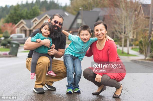 Two Native American parents and their children take a family walk through their suburban neighborhood