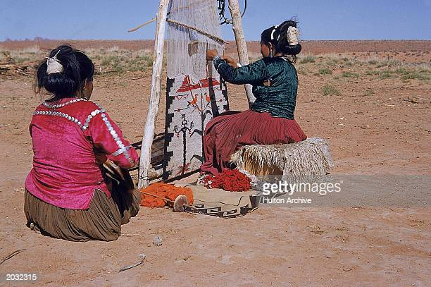 Two Navajo women use a loom to weave Monument Valley Arizona undated
