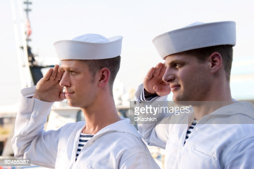 Two Navy sailors saluting on a ship