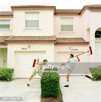 Two neighbours fighting with brooms over hedge : Stock Photo