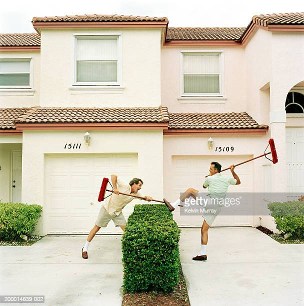 Two neighbours fighting with brooms over hedge