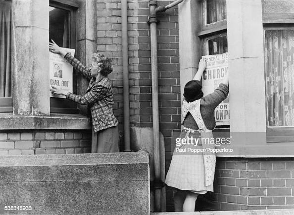 Two neighbours putting election posters in their windows in the runup to the General Election in Devonport Plymouth Devon 1950 The woman on the left...