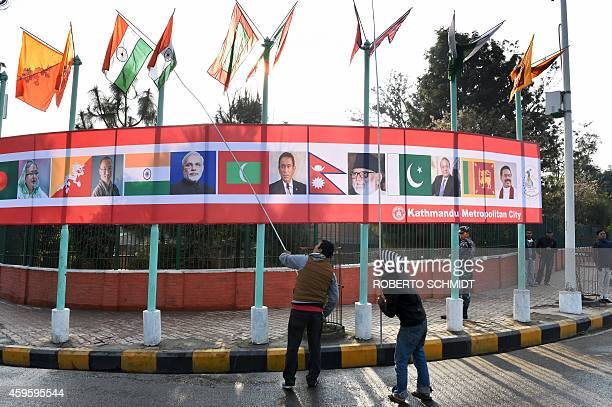 Two Nepalese workers use poles to untangle flags representing the SAARC nations near the main entrance of the venue hosting the opening session of...