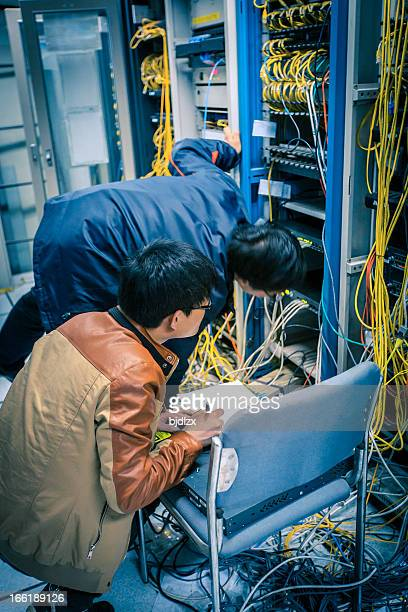 Two network administrators are working in the server room