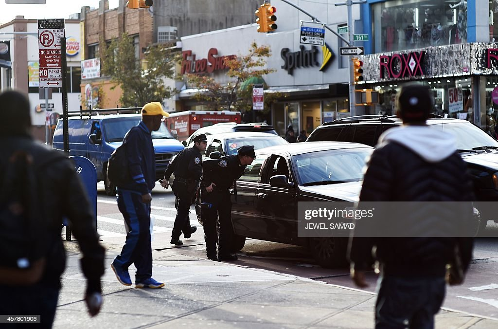 Two New York Police Department officers talk to the driver in a car near Jamaica Avenue and 162nd street in Queens on October 24 one day after a...