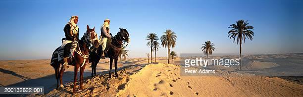 Two nomads riding horses across desert, standing on dune