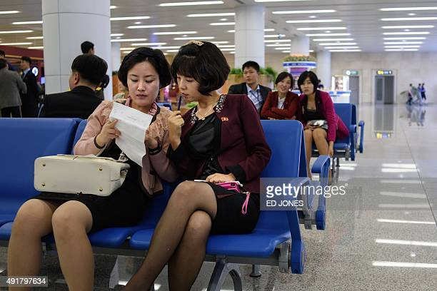 Two North Korean women sit in the arrivals at Pyongyang's International airport on October 8 2015 North Korea is gearing up for a lavish celebration...
