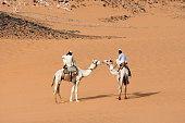 Two Nubian men dressed in thawbs riding dromedary camels in the Nubian desert of Sudan North Africa