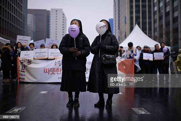 Two nuns hold balloons as they join environmental campaigners for a march in Seoul on November 29 2015 Environmentalists were marching as part of a...
