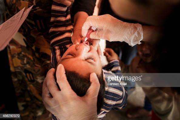 Two nurses give a crying child the Oral polio vaccine in a corner in a refugee camp in Suruc September 28 2014 south of Sanliurfa Turkey Islamic...