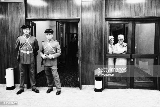 Two nurses look out the window from inside a hospital in Madrid whilst Spanish Civil Guard officers stand outside Spain 1975