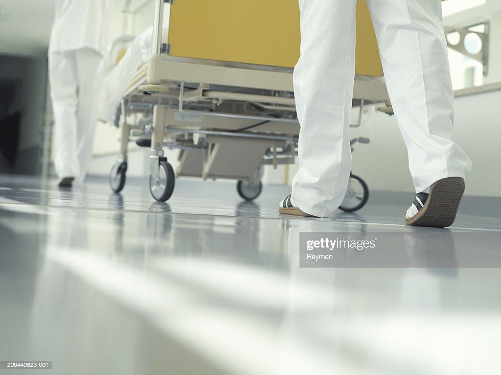 Two nurses wheeling hospital bed through corridor, low section : Stock Photo