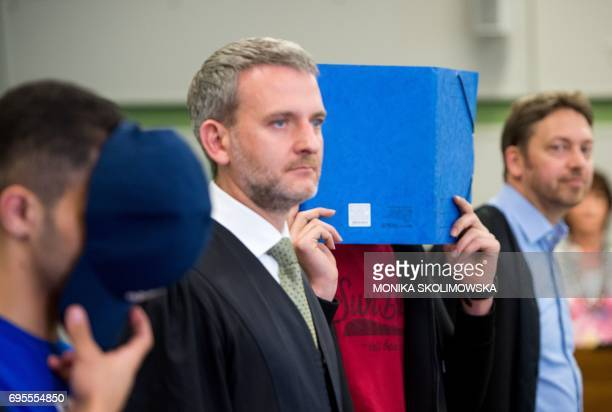 Two of six young men accused of setting fire to a sleeping homeless man stand next to their lawyers as they wait for their trial at court in Berlin...