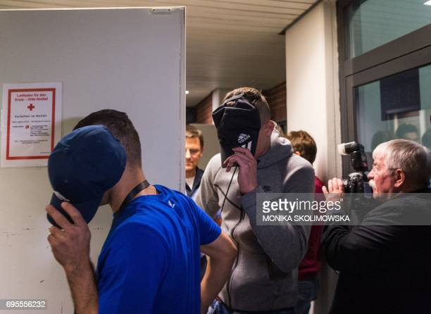 Two of six young men accused of setting fire to a sleeping homeless man hide their faces as they arrive for their trial at court in Berlin on June 13...