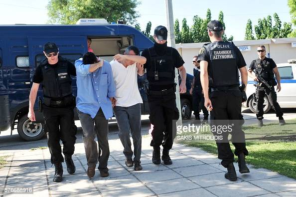 Two of the eight Turkish officers due to appear before a Greek prosecutor arrive escorted by police officers in Alexandroupoli northern Greece on...