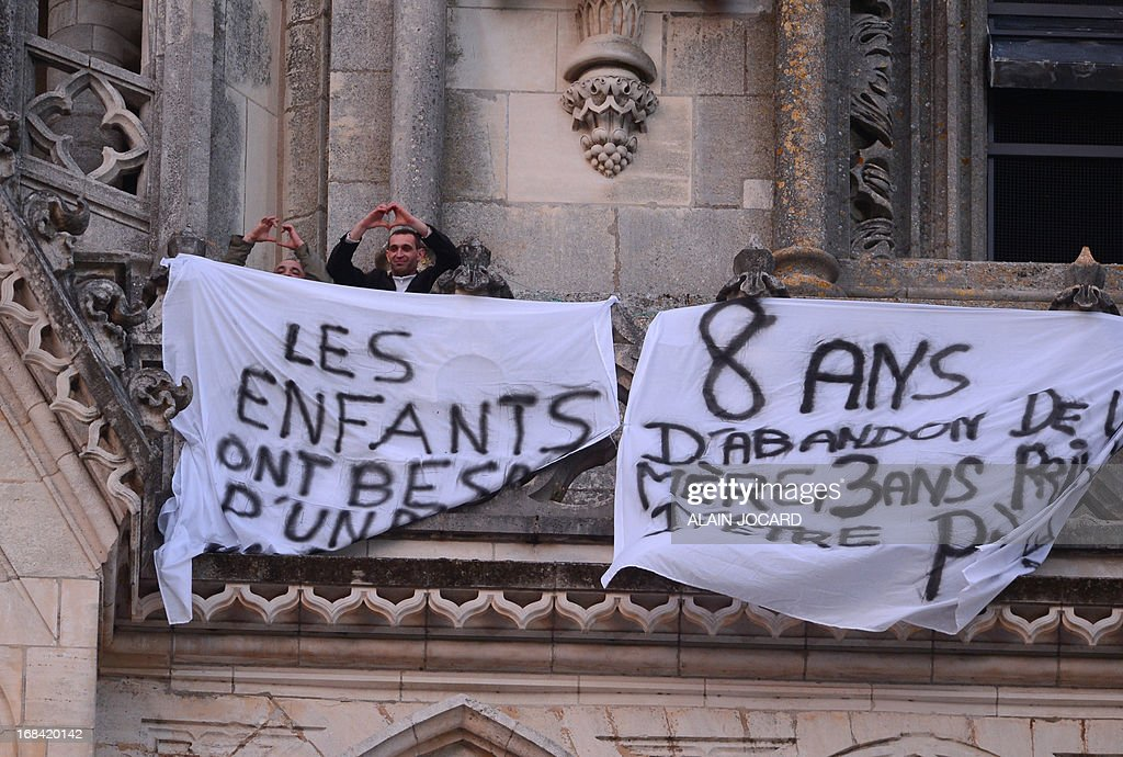Two of the four fathers who take action for their rights as parents, flash a heart-shaped sign next to banners on May 9, 2013 as they protest on a terrace on top of the cathedral in Orleans, western France. The group, whose members came from different places in France, previously planned a visit to the cathedral to enter it for their protest as divorced or separated parents.