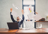 Two of young businessman trowing papers papers/sheets for work after finishing work, successful in business target in modern office, feeling happy, cheerful and relax