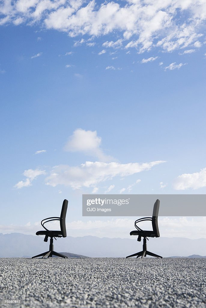 Two office chairs on a terrain full of pebbles : Stock Photo