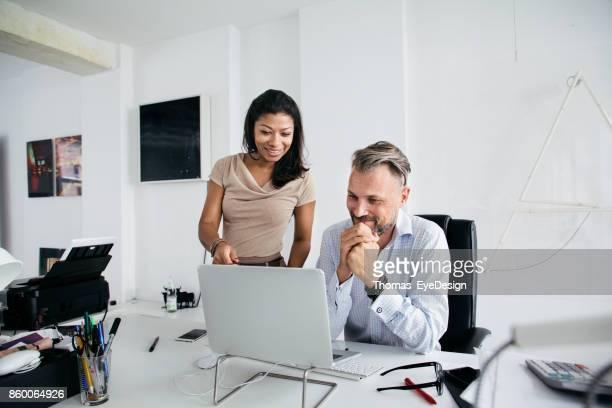 Zwei Bürokollegen Lächeln beim Computer betrachten