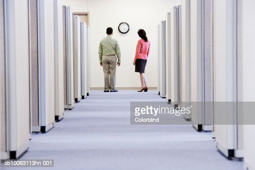 Two office colleagues watching time, rear view : Stock Photo
