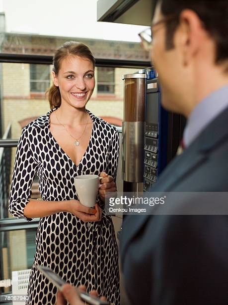 Two office people talking by the coffee maker.