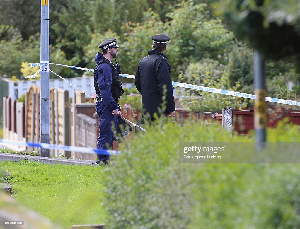 Two officers stand guard at the scene outside a house in Hattersley, Tameside where two female police officers were shot today on September 18, 2012 in Manchester, England. A local man Dale Cregan aged 29 has been arrested in connection with the shooting and two previous murders.