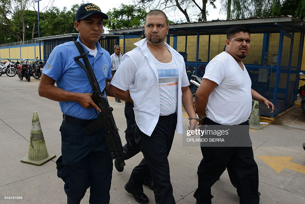 Two officials of Honduras' Immigration administration are arrested during the 'Operation Mesoamerica' in Tegucigalpa on June 28, 2016. The operation, which was performed simultaneously in the United States, Mexico, Nicaragua, El Salvador, Costa Rica, Panama and Honduras, aims at dismantling an international criminal structure dedicated to the trafficking of migrants. / AFP / ORLANDO