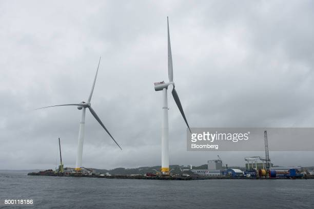 Two offshore floating wind turbines stand on the shoreline during assembly in the Hywind pilot park operated by Statoil ASA in Stord Norway on Friday...