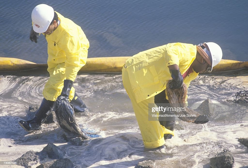 Two oil cleanup workers wade in oily water between a yellow oil barrier and a rocky shoreline clearing up oil with absorbent material after a spill at Orange County, California : Stock Photo