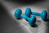Close-up of two old blue dumbbells for weight training or fitness on a gray gym floor