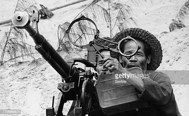 Two old fishermen from the village of nam ngan manning an antiaircraft machine gun to defend against american air attacks north vietnam 1968