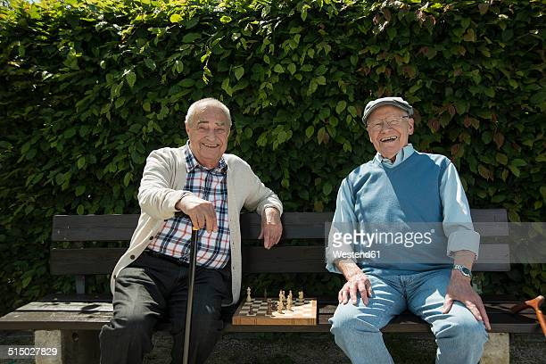 Two old friends sitting on park bench with chess