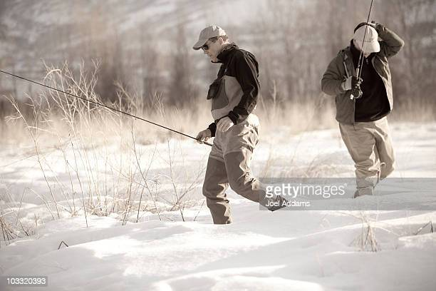Two old friends walk through the snow to fish on the Provo River in Utah during the winter.