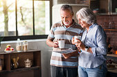 Sharing interesting news. Grey man pointing his wife at the information in newspaper while having morning tea